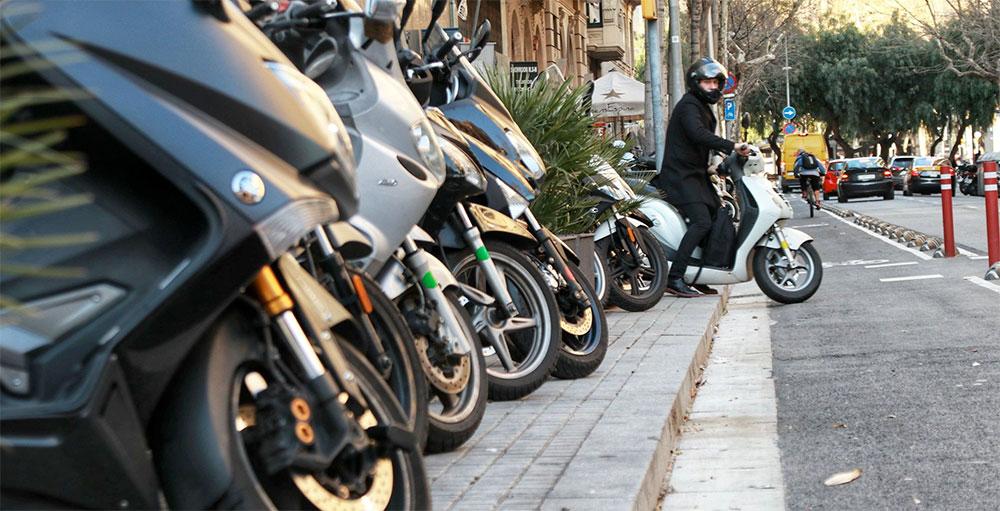 bicis y motos aparcando en la acera en Barcelona